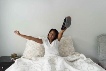Eine junge Frau wacht gerade auf, lächelt und hält eine Schlafmaske von Hupnos in der Hand.