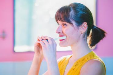 Eine Frau hat die Y-Brush zum Zähneputzen im Mund