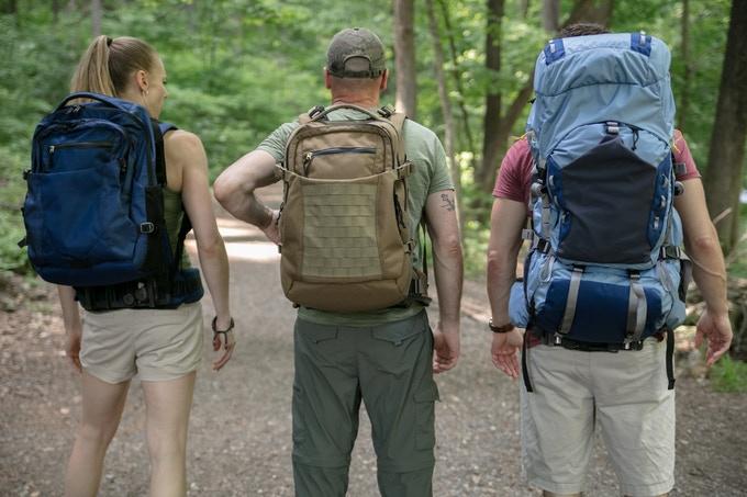 Drei Personen stehen mit dem Rücken zur Kamera in der Natur. Sie tragen jeweils ein Modell des Hoverglide.