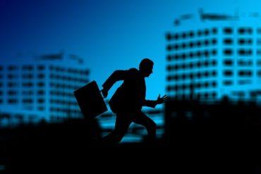 Ein Mann mit Aktentasche rennt vor der Silhouette einer Großstadt von links nach rechts