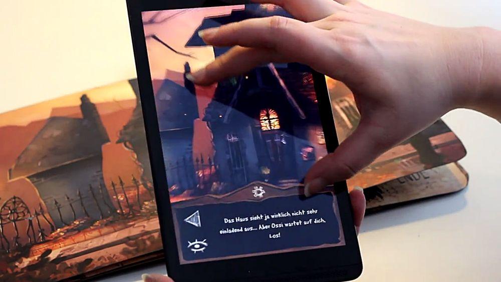 Ein Handybildschirm mit der App zu Ernas Unheil ist über dem Buch zum Spiel. Eine Hand bedient die App