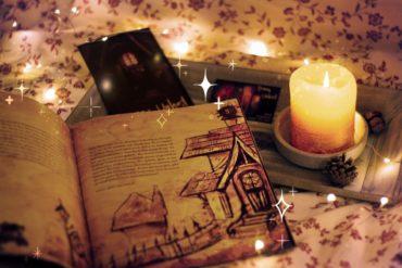 Das Buch Ernas Unheil liegt aufgeschlagen auf einem Tisch. Daneben steht eine Kerze