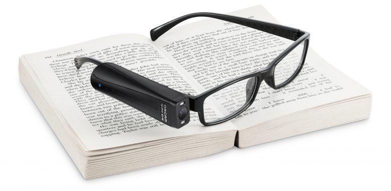 Die OrCam MyEye steckt an einer Brille, die auf einem offenen Buch liegt.