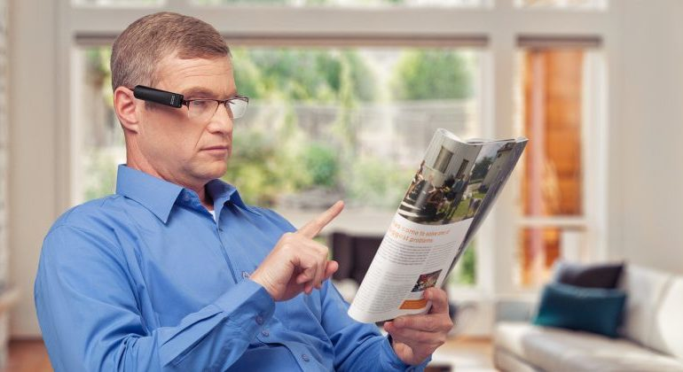 Ein älterer Mann sitzt im Stuhl. Er trägt eine Brille, an der die OrCam MyEye befestigt ist und zeigt auf eine Zeitung, die er in der Hand hält.