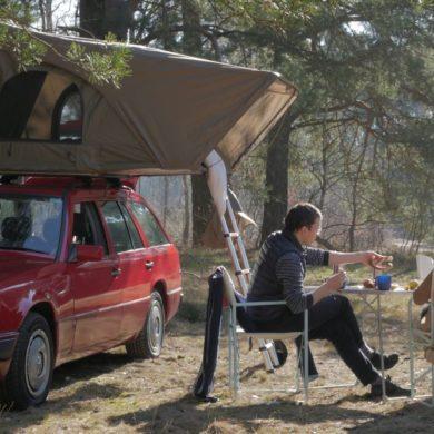Das Dachzelt steht auf einem Auto im Wald. Davor sitzen zwei junge Leute und trinken etwas.