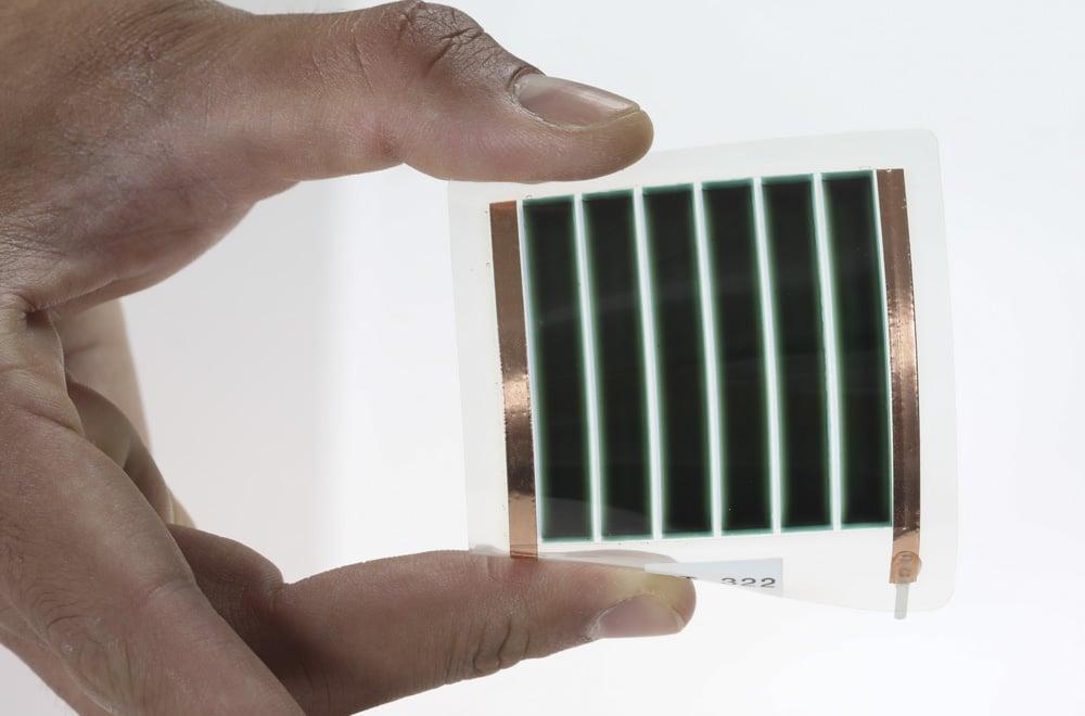Eine Hand hält ein kleines und biegbares Solarmodul von Dracula Technologies zwischen zwei Fingern